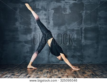 Young Sporty Woman Practicing Yoga, Doing One Legged Downward Facing Dog Pose Eka Pada Adho Mukha Sv
