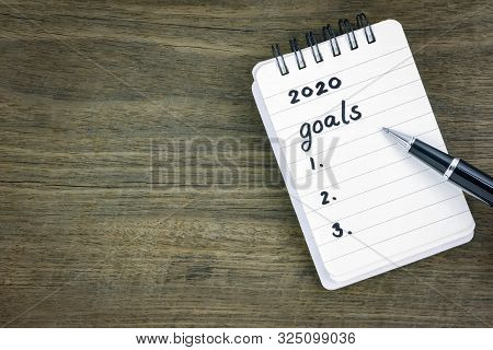 Top View 2020 Goals List On Notepad. Handwriting On Memo Paper Notebook With Black Pen Over Wooden T