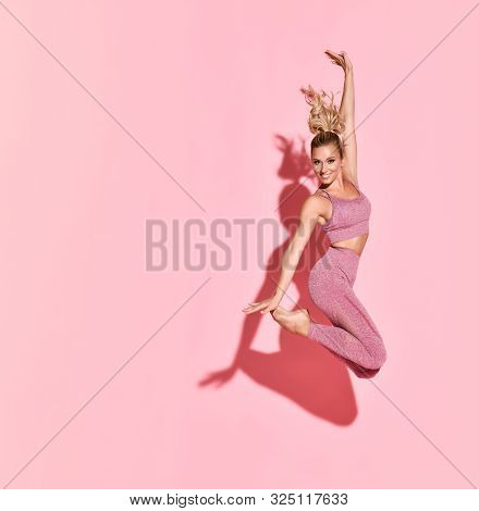 Happy Athletic Woman Jumping In Silhouette. Photo Of Sporty Woman In Fashionable Pink Sportswear On