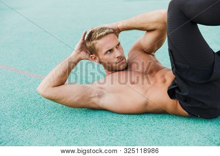 Image of young shirtless man lying at green sports ground and doing criss cross crunches