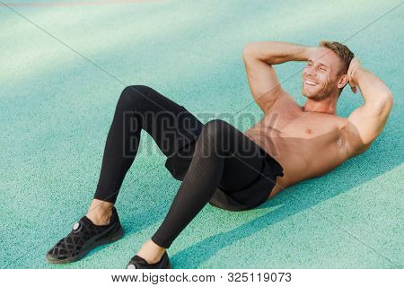 Image of caucasian shirtless man lying at green sports ground and doing criss cross crunches