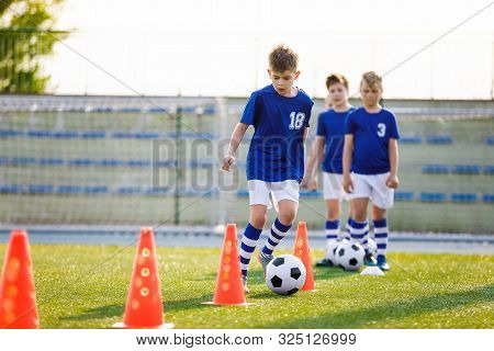 Football Training Dribbling Cone Drill. Young Boys Of School Junior Soccer Team Practicing On Grass