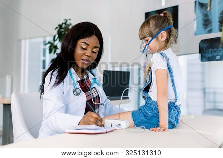 Young African Female Doctor Helping To Little Girl With Nebulizer Mask. Medical Doctor Applying Medi