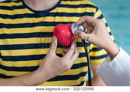 Woman Doctor Using Stethoscope Listen Heart Beat Sound From Red Heart Plastic On Hand Of Patient. Co