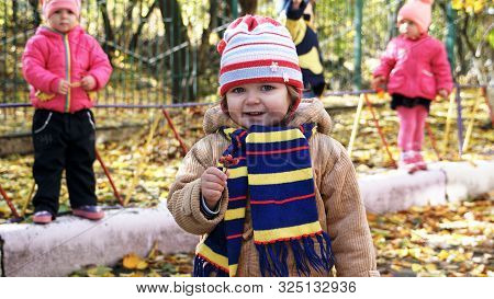Autumn Time. Little Smiling Child With Bunch Of Ashberry Dressed In Yeallow Jacket And Striped Scarf