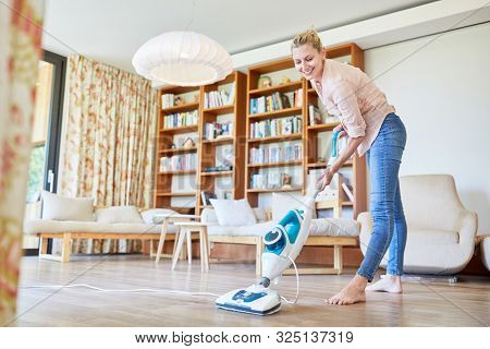 Housewife as a cleaning lady with steam cleaner in the living room at the floor cleaning