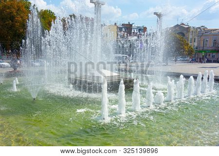 Waterworks Fountain With Water Sprays And Geysers On City Park Or Street. Autumn Day Time Freshness