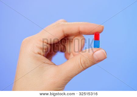 Red and blue bolus (capsule) in doctor hand, macro view