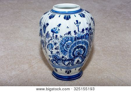 Hand Made Dutch Delft Blau (blue) Vase With Blue Designs And Porcelin China On An Isolated Beige Bac