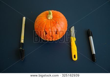 Little pumpkin with spiteful grimass, paper knife, pen, trowel over black background. Halloween concept, flat lay, top view. The process of making jack-o-lantern. flat lay. poster