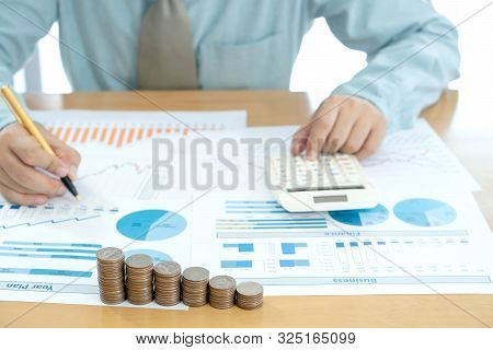 Businessman Analyzing Investment Charts And Pressing Calculator Buttons Over Documents