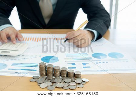 Businessman Using Calculator And Tablet With Stacked Coins Arranged