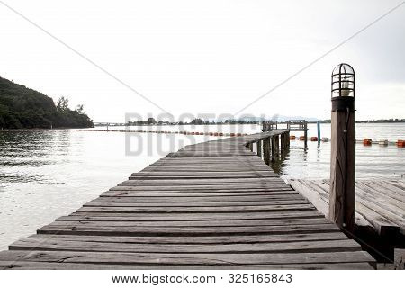 View Of A Wooden Pier On The Seashore With Clear Morning Sky And Sea