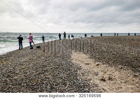 People Fishing On Danish Shore Of Oresund, Outside The Kronborg Castle.