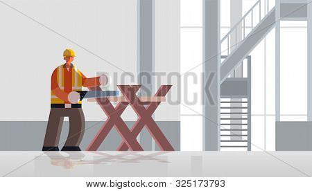 male builder carpenter using handsaw sawing log on sawbuck into lumber busy workman in uniform building concept construction site interior flat full length horizontal poster
