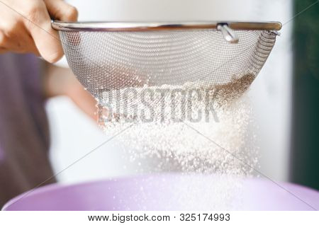 Woman Lour Sifting Through A Sieve For A Baking, Close Up