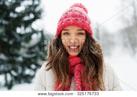 people, season and christmas concept - portrait of happy smiling teenage girl or young woman outdoors in winter park