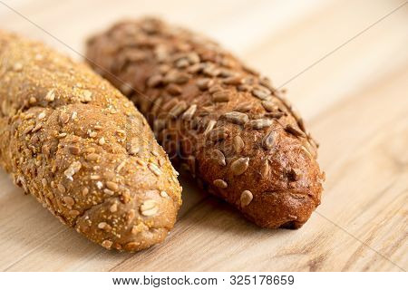 poster of Long whole wheat sunflower seed bread roll and long whole wheat sesame seed bread roll on light wood.