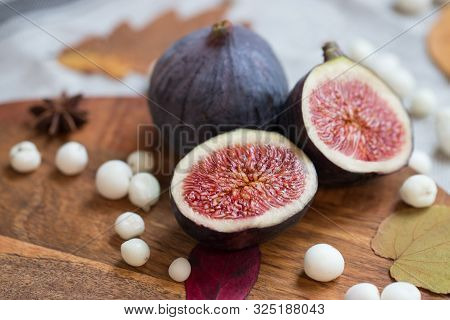 Cut Fresh Tasty Ripe Figs On Desk With White Snow Berry, Anise, Fallen Dry Leaves, Soft Focus. Figs