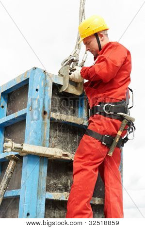 worker mounter assembling concrete formwork at construction site