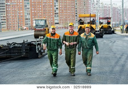 three happy road construction workers walking over asphalt paver machine