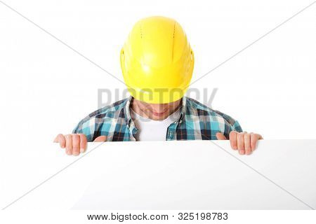 Builder man with yellow helmet on head holding blank board for advertisement.