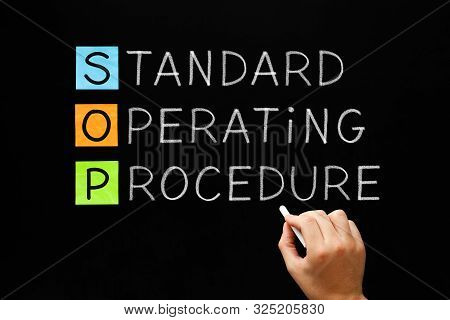 Hand Writing Sop Standard Operating Procedure Concept With White Chalk On Blackboard.