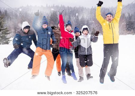 group portrait of young happy business people enjoying snowy winter day with snowflakes around them during a team building in the mountain forest