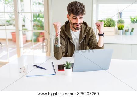 Young student man using computer laptop and notebook screaming proud and celebrating victory and success very excited, cheering emotion