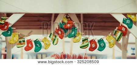 Advent Calendar. Christmas Decoration Bright And Colorfull Stockings Hanging Over Wooden Background.
