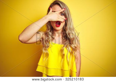Young attactive woman wearing t-shirt standing over yellow isolated background peeking in shock covering face and eyes with hand, looking through fingers with embarrassed expression.