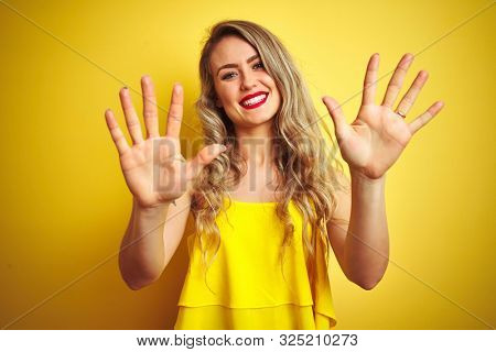 Young attactive woman wearing t-shirt standing over yellow isolated background showing and pointing up with fingers number ten while smiling confident and happy.