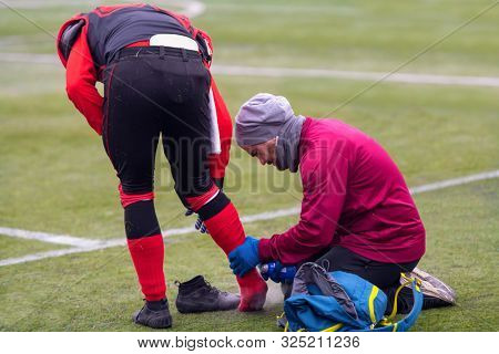 Sport medicine in action  Sports doctor using freezing spray while anesthetizing injured foot of a professional american football player on the stadium field poster