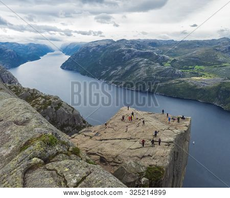Preikestolen Massive Cliff At Fjord Lysefjord, Famous Norway Viewpoint With Group Of Tourists And Hi