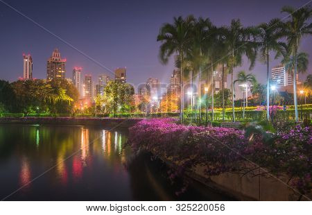 Lake With Calm Water Reflecting Nearby Buildings In South Part Of Benjakiti Public Park At Night In