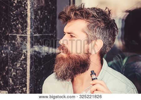 Bearded Brutal Male Smoking Electronic Cigarette. Mature Hipster With Beard. Hipster Man Hold Vaping