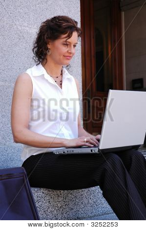 woman typing on laptop.