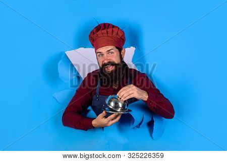 Cook Man With Cloche Through Paper. Professional Chef Holds Dish. Chef With Metal Cloche. Waiter Hol