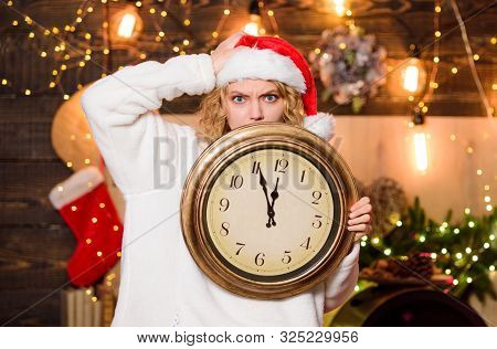 Time for winter party. Time for miracles. Few minutes left. New year countdown. Unexpectedly soon. Midnight concept. Make wish. Woman Santa hat hold vintage clock. Time to celebrate. Merry christmas poster