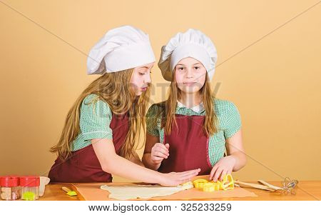 Young Bakers Following Baking Recipe. Small Bakers Rolling Paste On Kitchen Table. Little Girls Baki