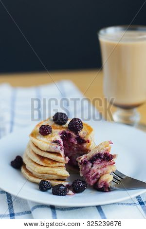 Eating Of Slapjack Or Oladyi With Black Raspberry With Fork On White Plate And Cocoa On Table With N