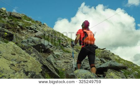 Woman Skyrunner Hiking In The Mountains With Nordic Walking Poles. Adventure And Exercising.