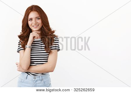 Intrigued And Creative Good-looking Female Team Member In Striped T-shirt, Touching Chin And Smiling