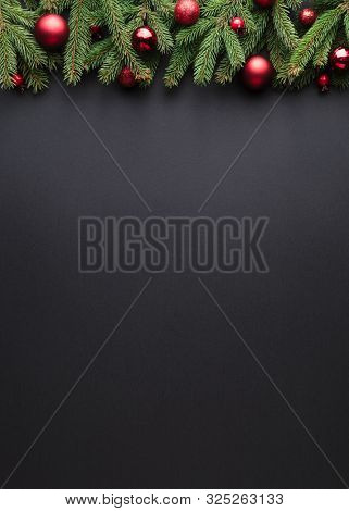 Christmas or New Year background. Fir branches Border with Christmas balls on a black background
