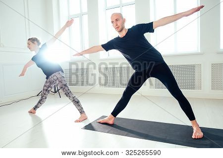 A Man And A Woman Practicing Yoga And In The Studio. Morning Asanas In Yoga Class. Team Work In The