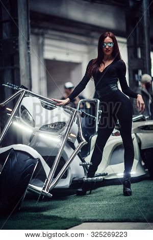 Fashionable Young Woman Standing Near The Steep Custom Trike