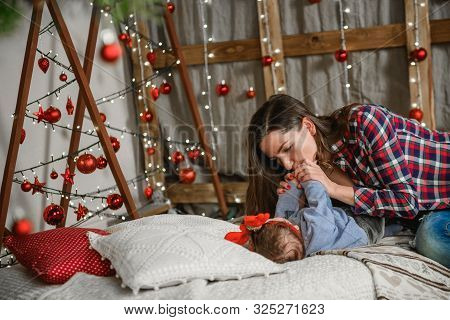Baby And Mom On Christmas Background. Happy Family Mom And Child Little Daughter Son And Christmas M