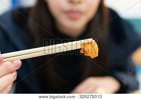 Holding Uni Sushi In Chopsticks. Sea Urchin(uni Sashimi) ,japanese Food.