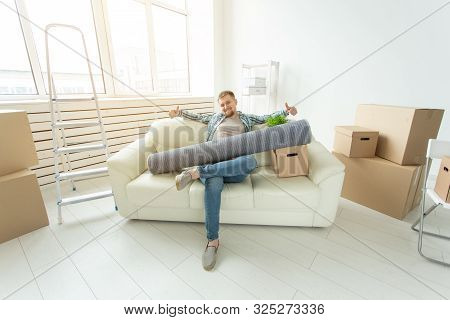 Positive Young Man Sitting On The Sofa With His Things In The New Living Room After The Move. Concep