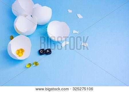 Empty cracked and broken open eggshells, yellow pills and word Ca - calcium poster